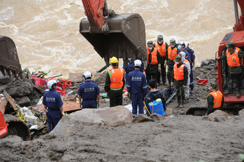 Rescuers stand during a silent tribute as they recover the body of a victim at the site of a landslide which hit buildings at a hydroelectric power station in Sanming, Fujian Province, China, May 9, 2016. REUTERS/Stringer ATTENTION EDITORS - THIS IMAGE WAS PROVIDED BY A THIRD PARTY. EDITORIAL USE ONLY. CHINA OUT. NO COMMERCIAL OR EDITORIAL SALES IN CHINA.