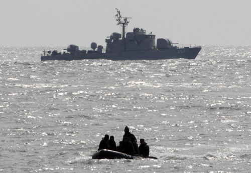 Members of South Korean Navy's Ship Salvage Unit (front) on a rubber boat and a naval patrol ship patrol to rescue possible survivors from sunken naval ship Cheonan off Baengnyeongdo, an island near the border with DPRK, March 27, 2010. (Xinhua News)